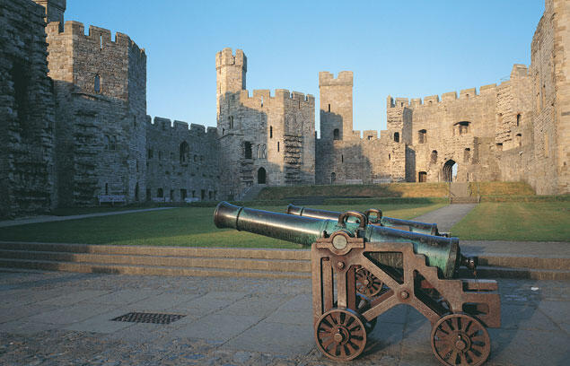 The interior of Caernarfon castle with two cannons in the foreground.